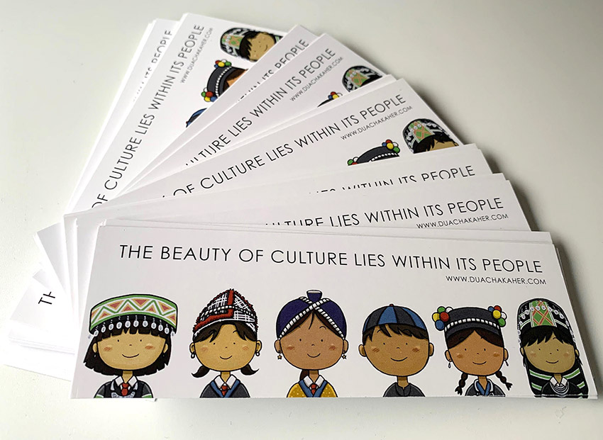 Hmong children wearing traditional dress on a bookmark illustrated by artist Duachaka Her