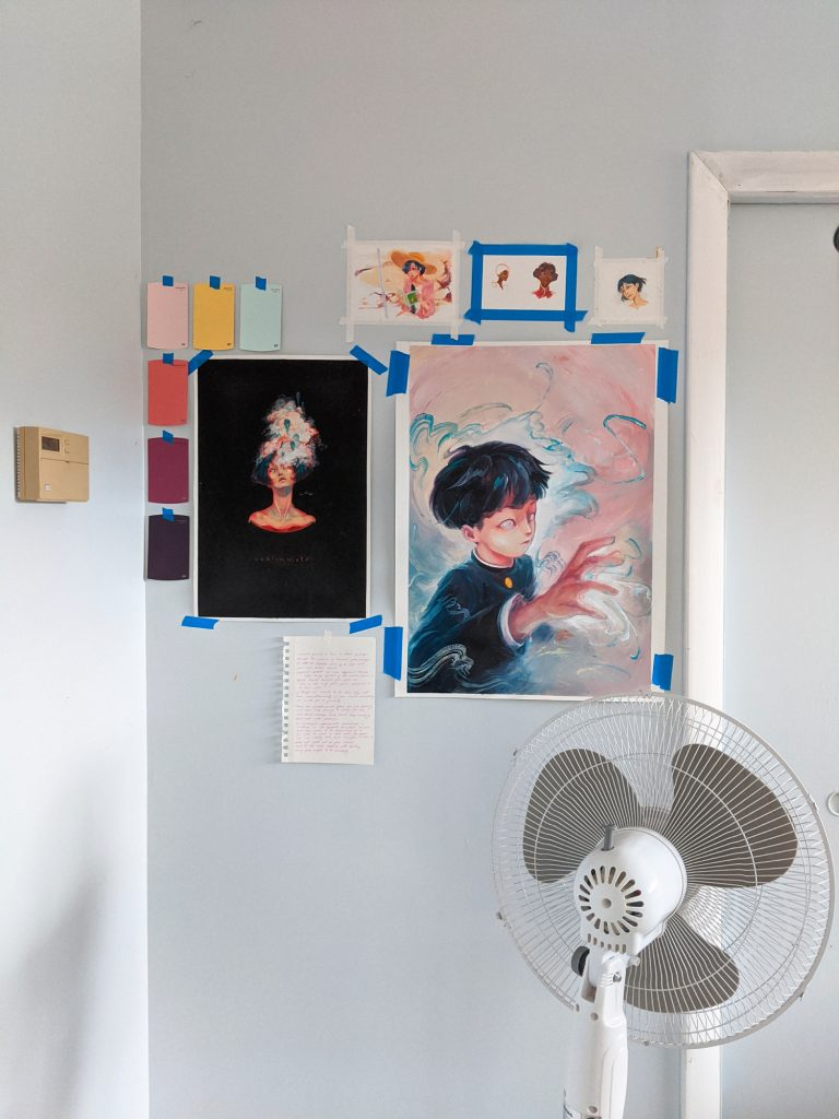 Serena Phu workspace with art tacked to the walls using painter's tape